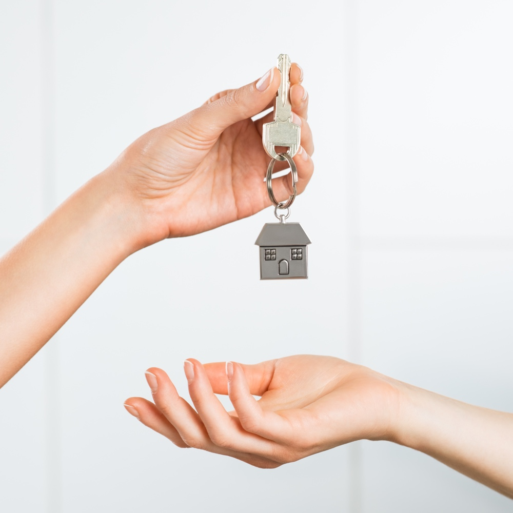 Closeup shot of a female hand receiving house key. Woman buying new home. Close up hand holding house key.