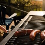 Person holding sausage on barbecue grill